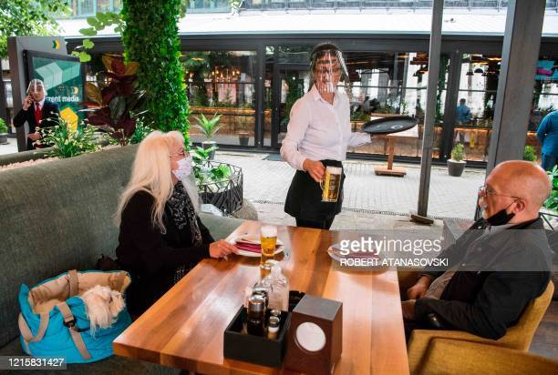 Waiter wearing a face shield serves drink to customers at a restaurant in Skopje on May 28, 2020. - Bars and restaurants opened their doors on May 28...