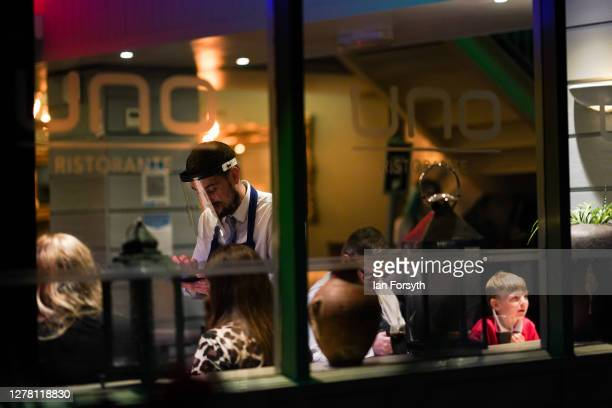 Waiter wearing a face shield takes a customers order in a restaurant on Linthorpe Road on October 02, 2020 in Middlesbrough, England. The mayor of...