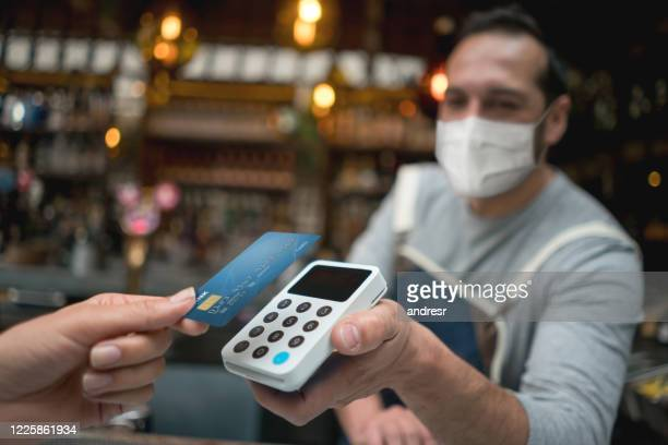waiter wearing a facemask while getting a contactless payment at a restaurant - nfc stock pictures, royalty-free photos & images