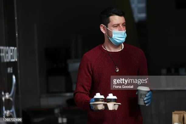 A waiter wearing a mask delivers takeaway coffee to customers waiting outside Dizengoff cafe in Ponsonby on August 13 2020 in Auckland New Zealand...