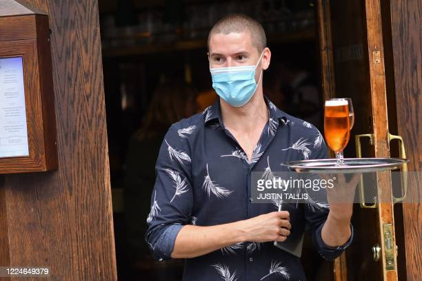 A waiter wearing a protective face covering brings out drinks to customers outside a cafe in Soho in London on July 4 as the Soho area embraces...