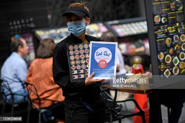 "Waiter wearing a protective face mask displays ""eat out to help out"" information in a restaurant in the chinatown area of Soho in London on August 26..."