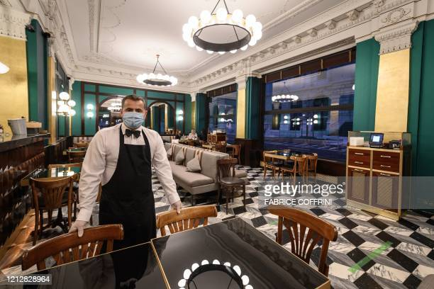 A waiter wearing a protective face mask poses in the nearly empty restaurant Le Lyrique cafe brasserie late on May 12 in Geneva on the day after...