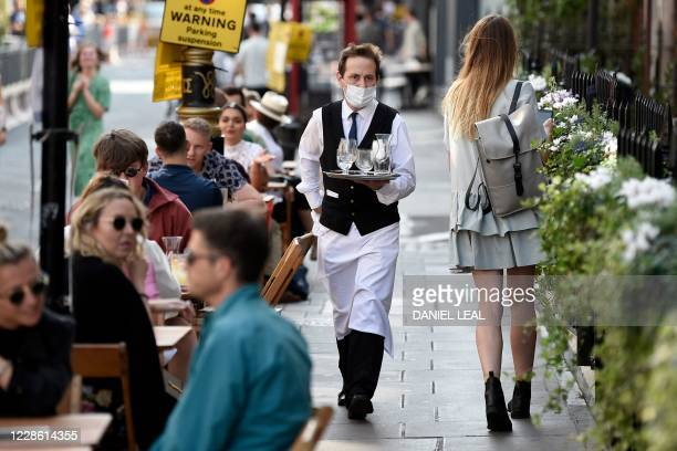 Waiter wearing a protective face mask serves customers at tables outside a restaurant in Soho, in London on September 20, 2020 as the British...