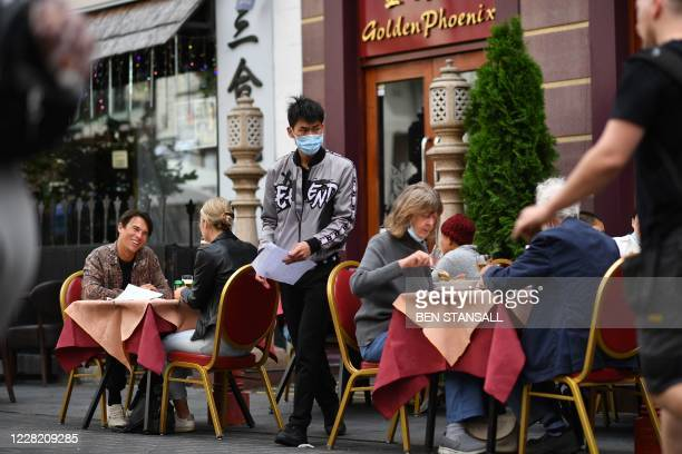Waiter wearing a protective face mask serves customers eating lunch at the outside tables of a restaurant in the chinatown area of Soho in London on...