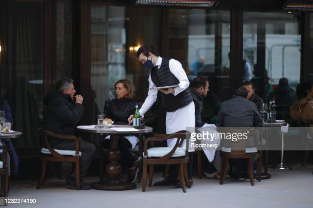 Waiter wearing a protective mask assists customers sitting in the outdoor dining area of a restaurant in Covent Garden in London, U.K., on Monday,...