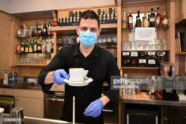 A waiter wearing a respiratory mask as part of precautiobary measures against the spread of the new COVID19 coronavirus hands a capuccino at a cafe...