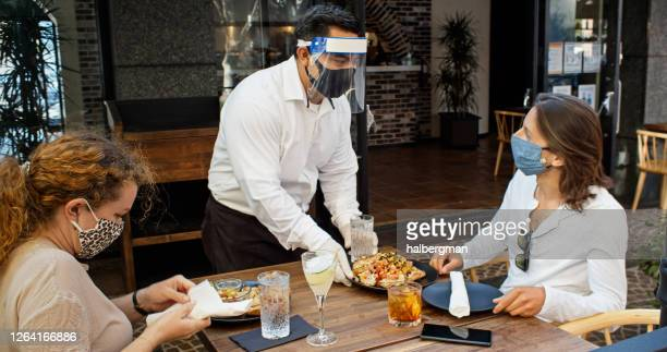 waiter wearing ppe during covid-19 pandemic serving food to diners wearing masks - restaurante imagens e fotografias de stock