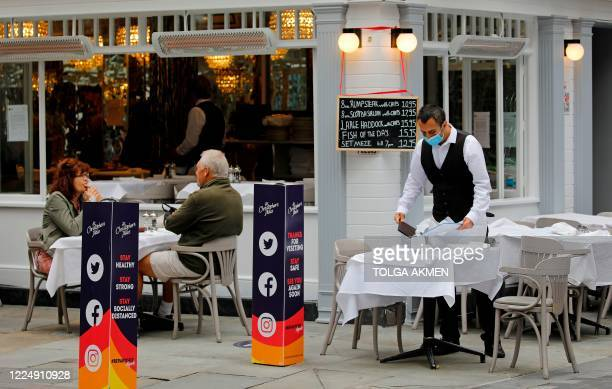 A waiter wearing PPE of a face mask or covering as a precautionary measure against spreading COVID19 works at a recently reopened restaurant in...