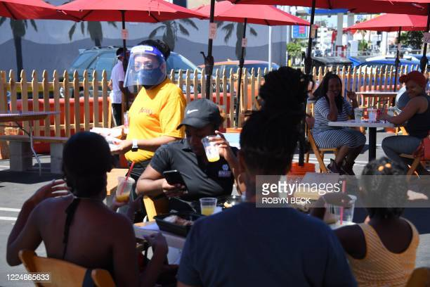A waiter wearing protective gear serves food to customers on the patio at Pann's an iconic Los Angeles California restaurant and coffee shop on July...
