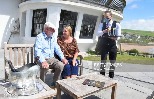 A waiter wearing protective mask serves drinks to guests at the Burgh Island Hotel on July 07 2020 in BigburyonSea United Kingdom The Art Deco Burgh...