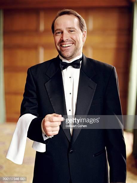 Waiter wearing tuxedo, holding cloth napkin over arm, portrait