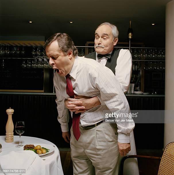Waiter with arms around choking man's stomach in restaurant