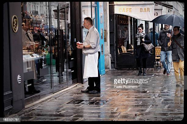 CONTENT] A waiter with coffee cups waiting for a client