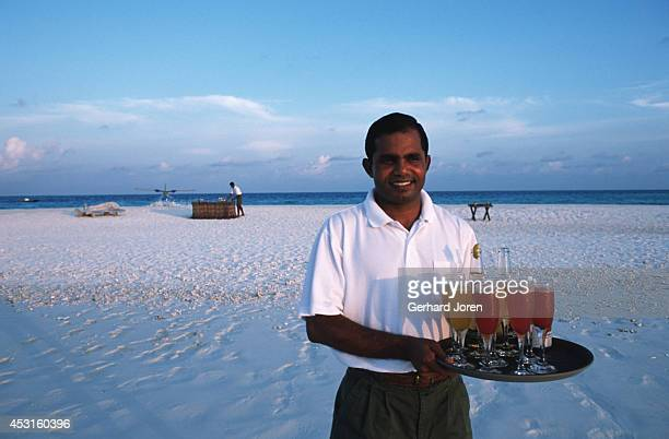A waiter with drinks for guests at a party on a sand bank at Soneva Fushi Resort Spa a 30minute plane ride from Male the capital of the Maldives...