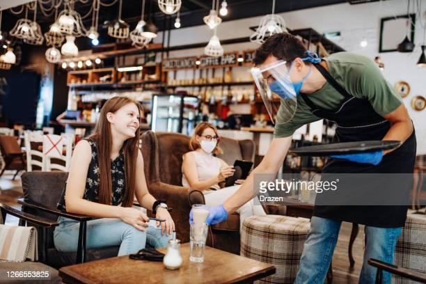 waiter with face shield and protective gloves serving customer in cafe after reopening - opening event stock pictures, royalty-free photos & images