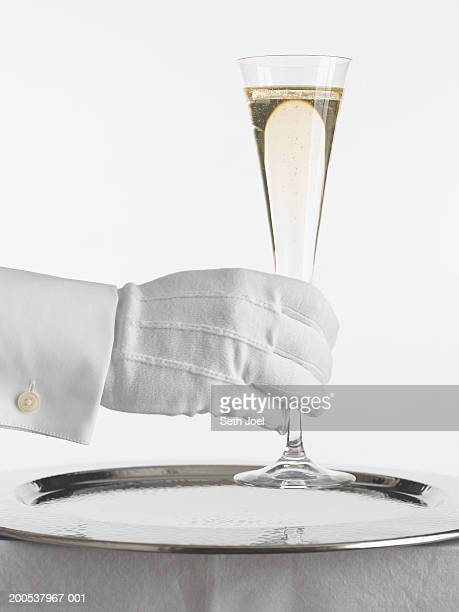 Waiter with glove holding glass of champagne