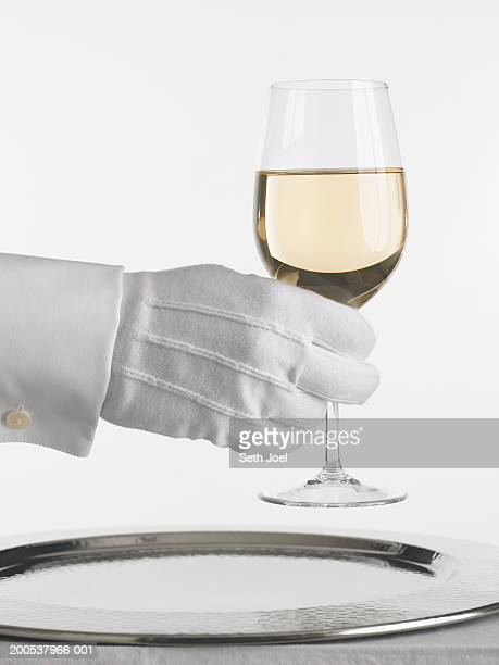 Waiter with glove holding glass of white wine