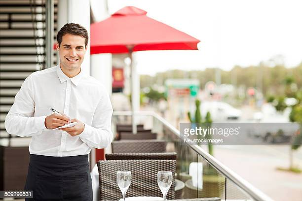 Waiter With Pen And Order Pad Smiling In Restaurant