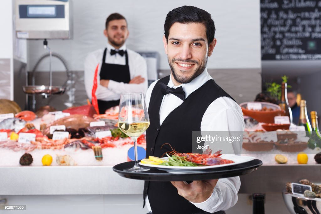 Waiter with serving tray in fish restaurant : Stock Photo