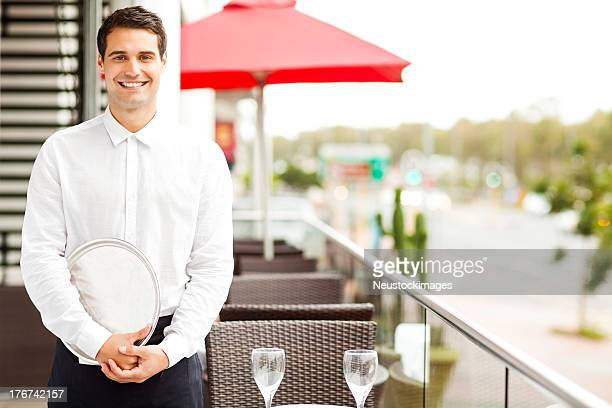 Waiter With Serving Tray Smiling In Restaurant