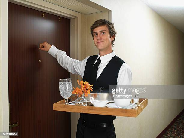 Waiter with tray knocking on door