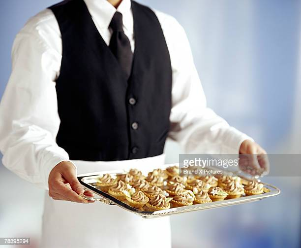 Waiter with tray of pastry