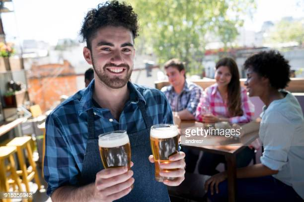 Waiter working at a bar serving beers to customers looking at camera smiling