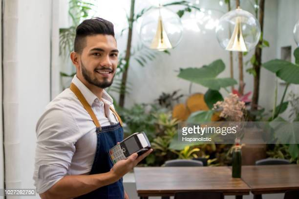 Waiter working at a restaurant holding an eftpos