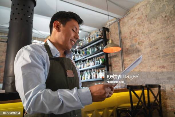 waiter working at a restaurant holding the menu - hispanolistic stock photos and pictures