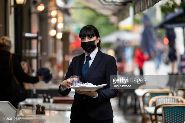 Waiter works at a restaurant/cafe bar near Oxford Street on October 13, 2020 in London, England. London Mayor Sadiq Khan said today that the city...