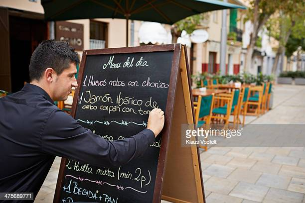 Waiter writing sign with traditional tapas dishes