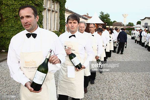Waiters attend the beginning of 'La Fete de la Fleur' dinner with a bottle of Haut Brion 2006 in the hand at Chateau de Lascombes on June 23 2011 in...