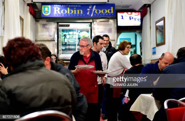 Waiters clear plates and serve dishes during a free dinner at the Robin Hood restaurant in Madrid on December 1 2016 Launched this week by 'Peace...