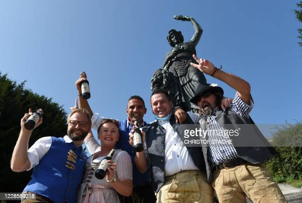 Waiters from the traditional Oktoberfest beer festival pose in front of the Bavaria monument at the Theresienwiese in Munich, southern Germany, at...