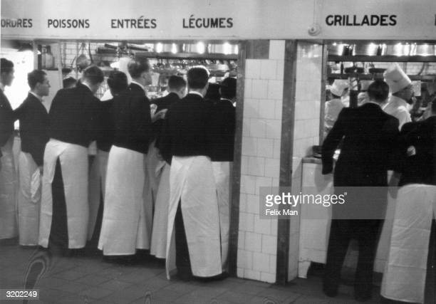Waiters give their orders in the main restaurant kitchen at the Savoy Hotel London Original Publication Picture Post 488 Savoy Hotel unpub