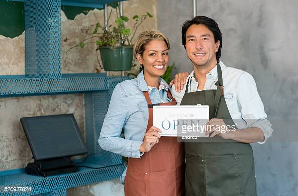 Waiters holding an open sign at a restaurant