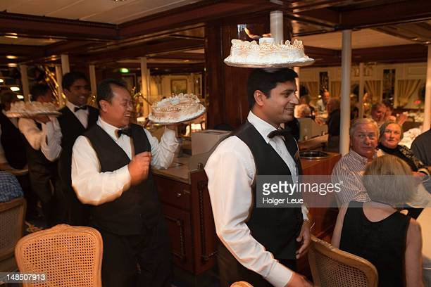 Waiters parading with ice cream cakes at Captain's Dinner in dining room aboard sailing cruiseship Star Flyer (Star Clippers Cruises) while cruising in the Pacific Ocean.