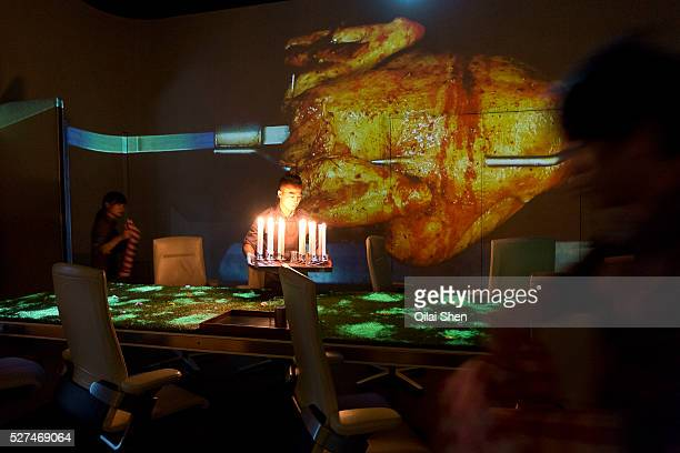 Waiters prepare for dinner as projections adorn the dining room wall of Chef Paul Pairet's Ultra Violet restaurant in Shanghai, China on 28 September...