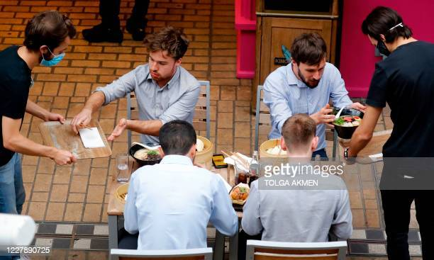 Waiters serve customers' their food and cutlery as diners sit at tables outside a restaurant in London on August 3 as the Government's Eat out to...