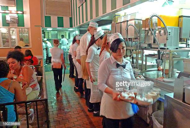 Waiters serve patrons at Cafe du Monde in New Orleans Louisiana