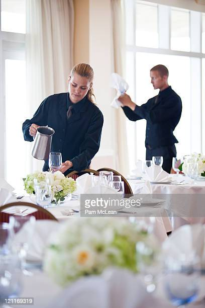 Waiters setting banquet tables