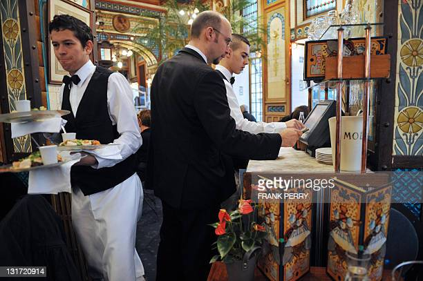 Waiters work during the midday service on November 7 2011 at the La Cigale brasserie in the French western city of Nantes As part of a...