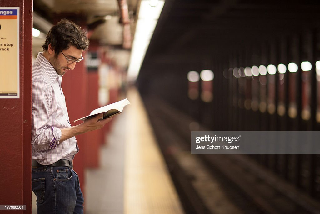 Waiting and Reading in the Subway : Stock Photo