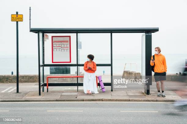 waiting at bus stop - waiting stock pictures, royalty-free photos & images