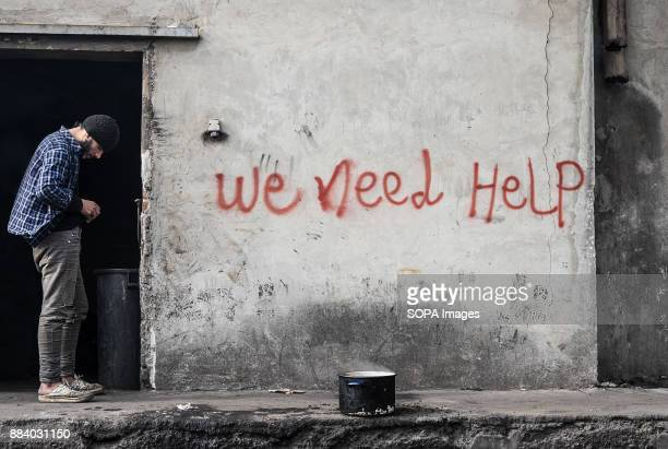 THE BARRACKS BELGRADE SERBIA Waiting for a pot of tea to cool down an Afghan refugee stands by the open door to an illegal refugee camp Thousands of...