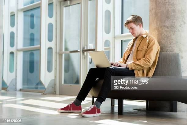 waiting for class, male student sits to work on laptop - community college stock pictures, royalty-free photos & images