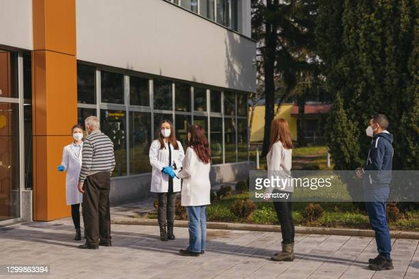 waiting for coronavirus vaccination - queuing stock pictures, royalty-free photos & images