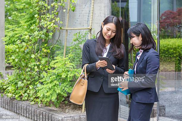 Waiting for Ride Sharing Service Professional Businesswomen Check Mobile Application