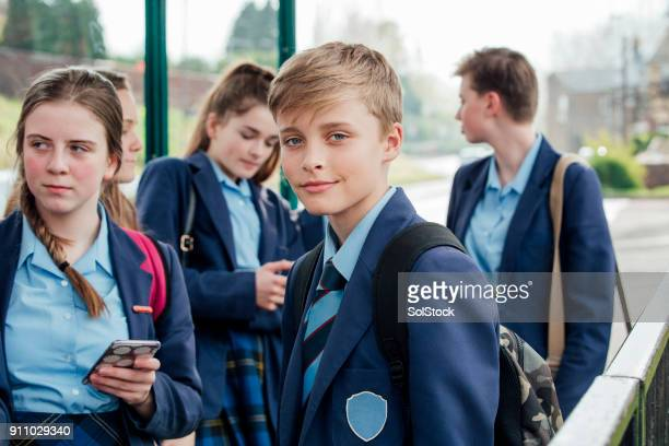 waiting for the bus - schoolboy stock pictures, royalty-free photos & images